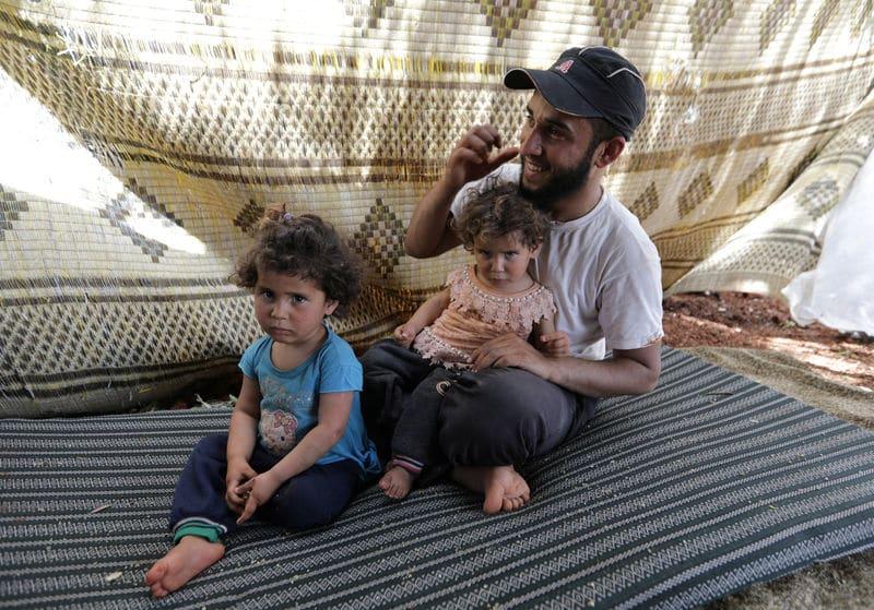 عائلة سورية تجتاز الأراضي الزراعية فرارا من هجمات إدلب